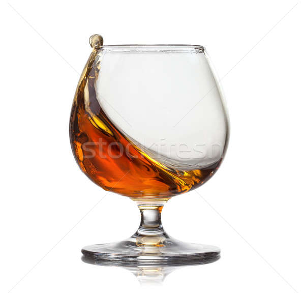 Splash of cognac in glass isolated on white background Stock photo © artjazz