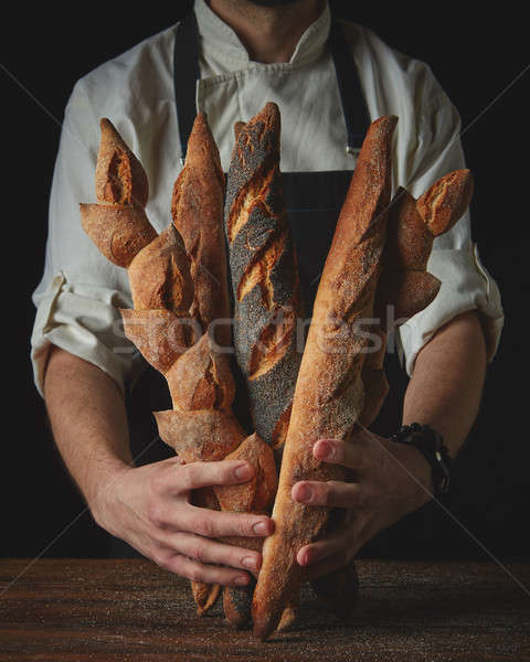 Hands of man holding baguettes Stock photo © artjazz