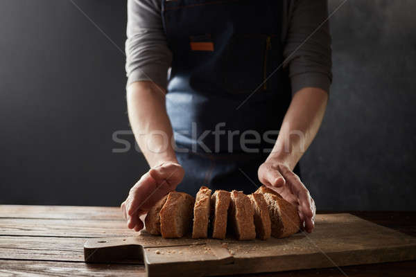 Wholegrain rustic bread. Chef hand cutting homemade bread sliced. Stock photo © artjazz