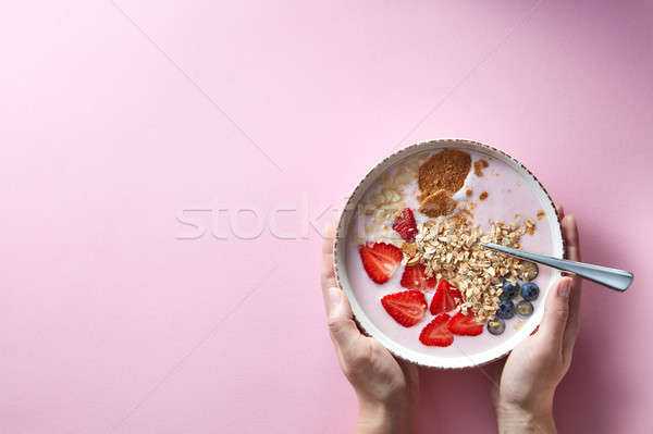 Woman's hands holding a bowl of organic yogurt smoothie with strawberries, banana, blueberry, oat fl Stock photo © artjazz