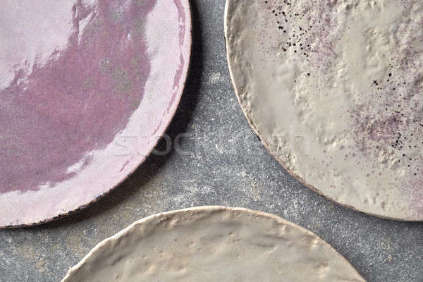 The porcelain vintage plates handmade on a gray marble table. Stock photo © artjazz