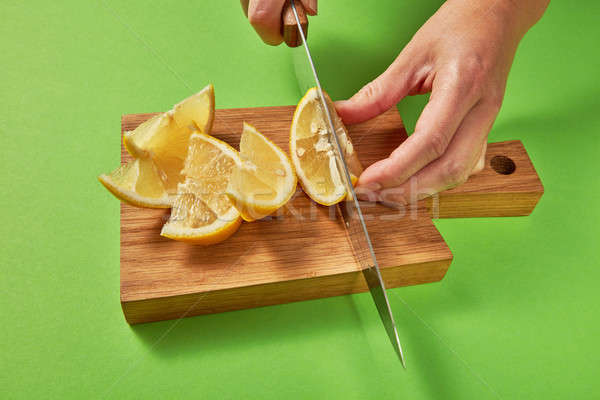 Female hands cutting a yellow ripe lemon for preparing homemade fresh cocktail on green background. Stock photo © artjazz