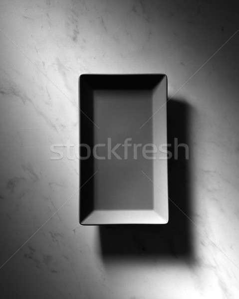 Black rectangular empty plate presented on a gray marble background with shadows, space for text. To Stock photo © artjazz