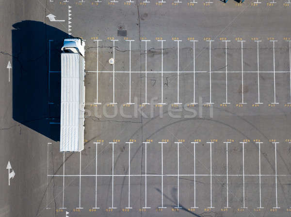 A long truck in a parking lot with markings for loading with building materials with sharp shadows o Stock photo © artjazz