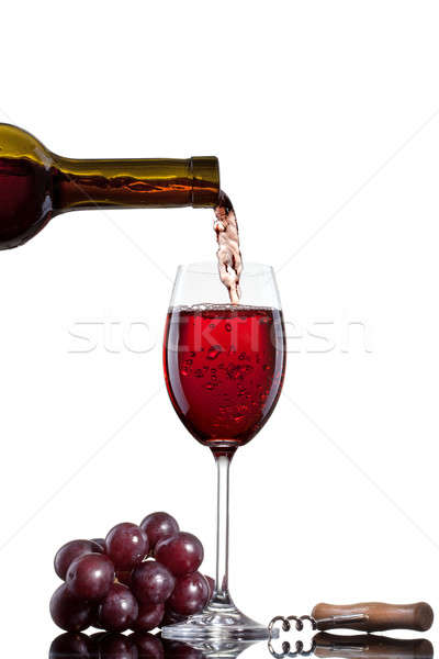 Red wine pouring into glass with grape isolated on white Stock photo © artjazz