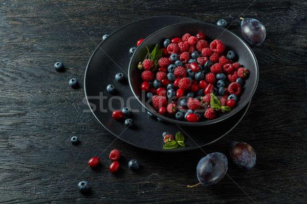 raspberries, blueberries, plum and dogwood. fresh berries on plate Stock photo © artjazz