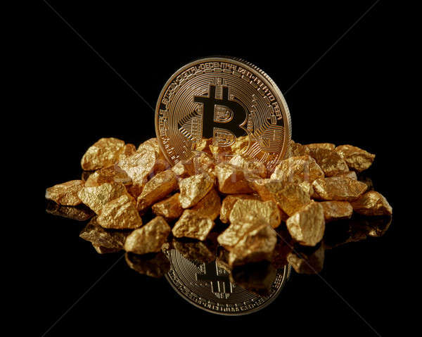 Studio shot of Bitcoin with gold nugget on a black reflective background .Digital virtual currency Stock photo © artjazz
