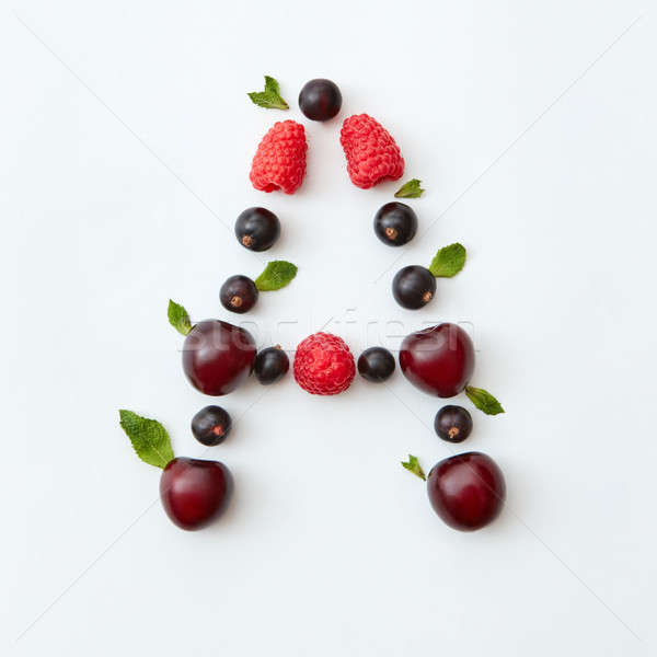 Berries pattern of letter A english alphabet from natural ripe berries - black currant, cherries, ra Stock photo © artjazz