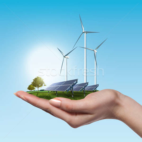 Wind turbines and solar panels in female hand Stock photo © artjazz