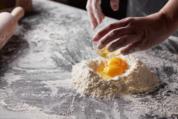 women's hands is cooking dough for baking on a kitchen table. Stock photo © artjazz