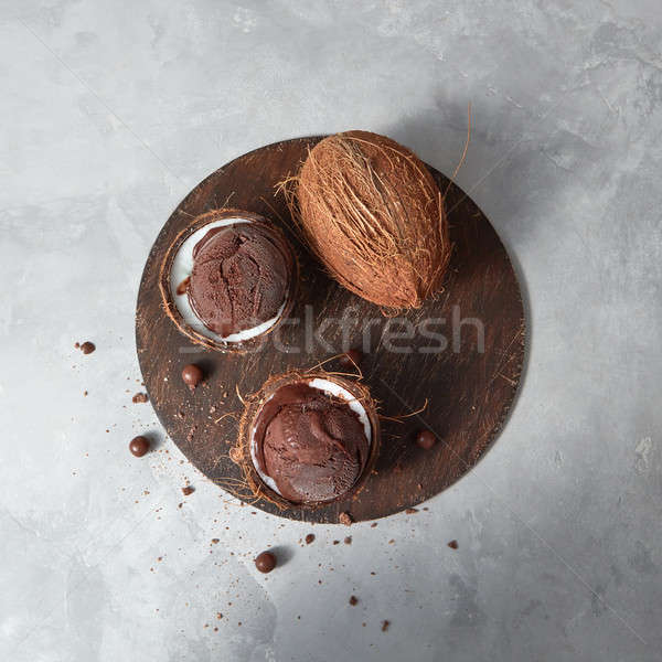 Two coconut halves with frozen fresh ice cream and whole coconut Stock photo © artjazz