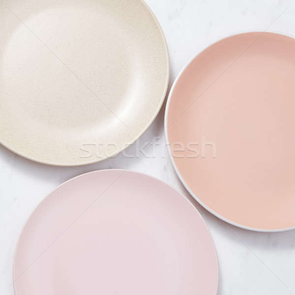 Porcelain empty plates on a gray marble table. Multi-colored ceramic handmade dishes. Top view. Stock photo © artjazz