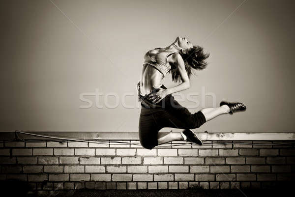 black and white photo of girl jumping on the roof Stock photo © artjazz