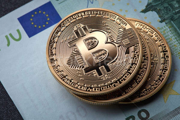 Three gold coins bitcoin stack on paper euro bill Stock photo © artjazz