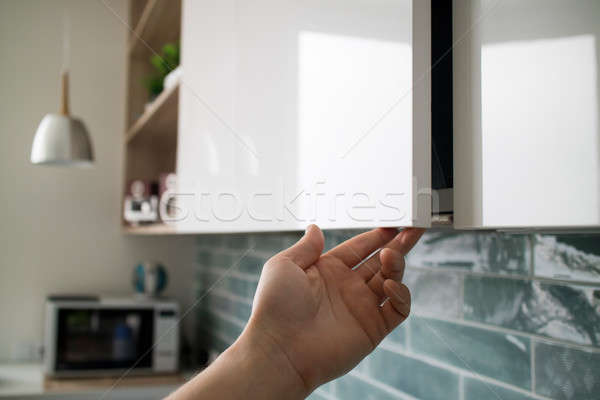 Kitchen interior with modern furniture. The man opens a modern hanging cabinet for a kitchen without Stock photo © artjazz