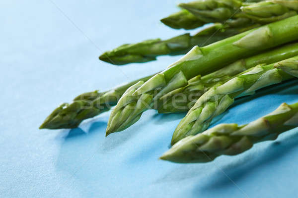 A lot of fresh asparagus on the blue background. Stock photo © artjazz