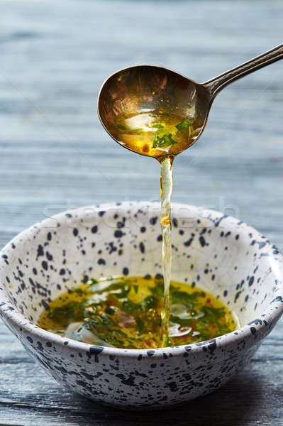 Homemade salad dressing with olive oil, vinegar, greens and spices pour from a spoon into a bowl on  Stock photo © artjazz
