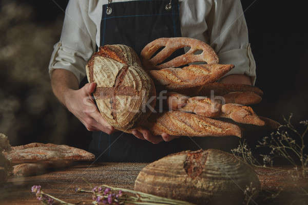 Baker in black apron holds variety of bread Stock photo © artjazz