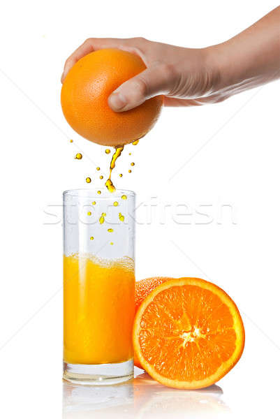 Stock photo: squeezing orange juice pouring into glass isolated on white