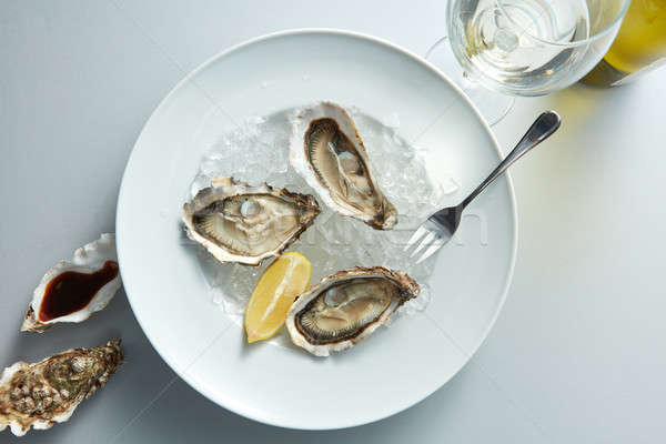 Seafood. Delicious oyster with lemon Stock photo © artjazz
