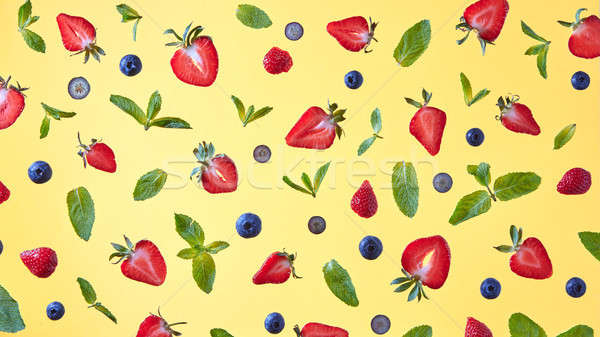 Wild strawberry, blueberry and mint leaves over yellow background, top view Stock photo © artjazz