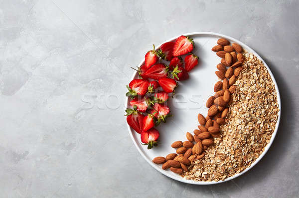 Plate with raw oatmeal, nut and strawberry on a gray concrete background. Ingredients for a healthy  Stock photo © artjazz