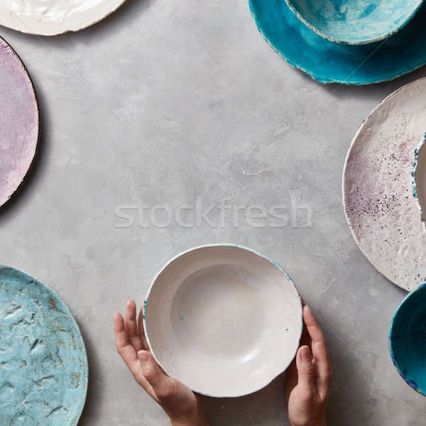 Colorful porceain vintage handmade dishes on a marble table with copyspace. Woman hands take a white Stock photo © artjazz