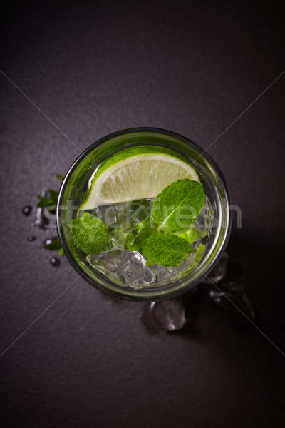 Tradition Summer drink mojito with lime and mint in glass on dark stone background Stock photo © artjazz