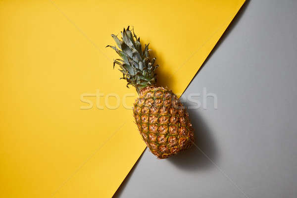 Flat lay view of tropical Pineapple fruit single on a duotone yellow-grey background Stock photo © artjazz