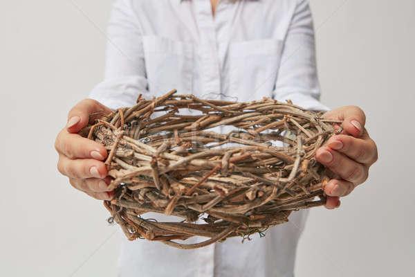 Lány tart koszorú kezek ágak szürke Stock fotó © artjazz