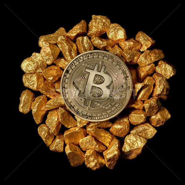 Bitcoin on mound of gold nuggets on a black background, bitcoin cryptocurrency concept Stock photo © artjazz