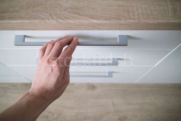 detail man hand is open of a laminate stylish kitchen drawer Stock photo © artjazz