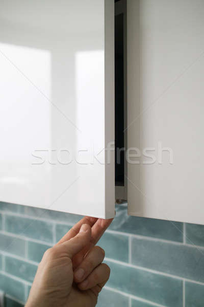 man hand opening or closing kitchen cabinet door Stock photo © artjazz