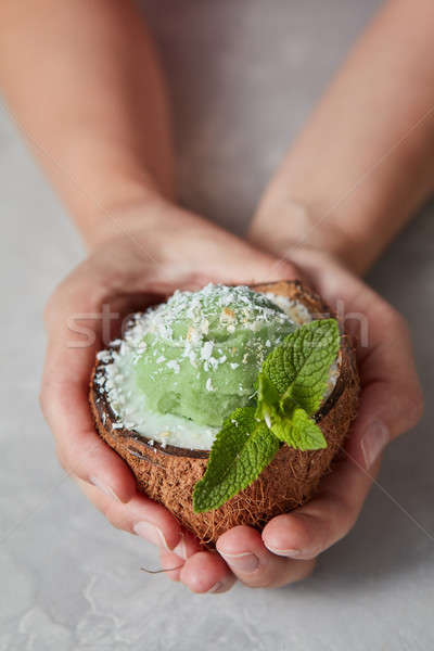 Woman hands hold frozen green sorbet in the coconut shell with f Stock photo © artjazz