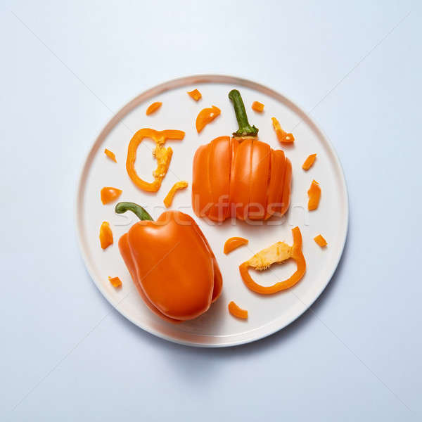 yellow peppers slice and half on white plate isolated on gray Stock photo © artjazz