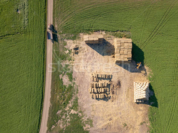 Aerial view from drone into area with stacks of straw after harvesting the grain and dirty road with Stock photo © artjazz
