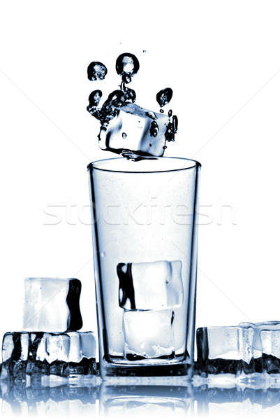 Stock photo: ice cubes dropped into glass with bubbles isolated on white