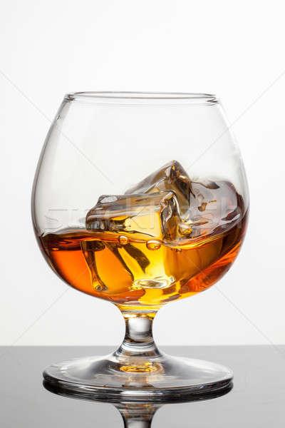 Splash of whiskey with ice in glass isolated on white background Stock photo © artjazz