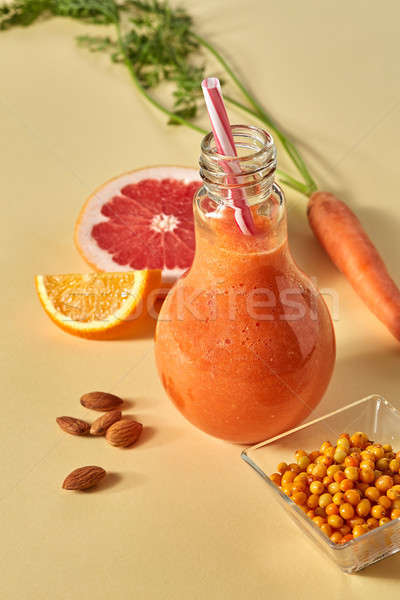Citrus vegetable smoothies with berries and nuts in a glass on an orange paper background Stock photo © artjazz