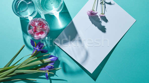 A bouquet of flowers with vases and a white sheet of paper on a blue background Stock photo © artjazz
