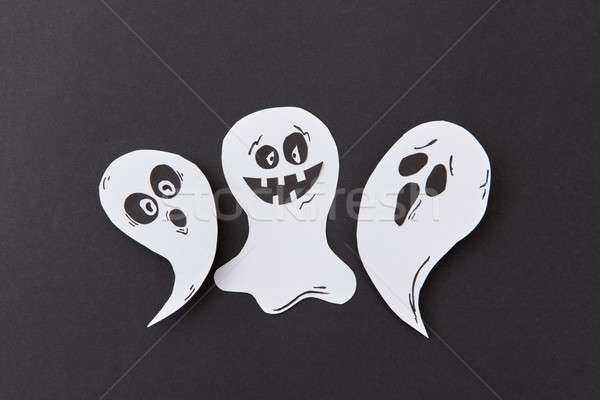 Halloween party card with paper handmade laughing flying scary specters, spirits on a black backgrou Stock photo © artjazz