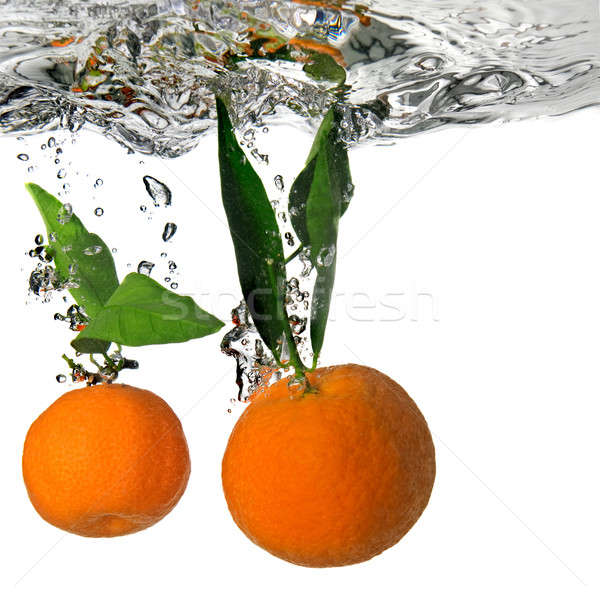 tangerine dropped into water with bubbles on white Stock photo © artjazz