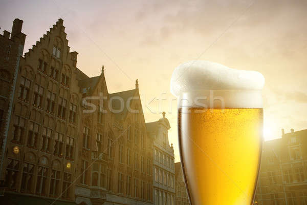 Glass of beer against silhouettes of houses in Bruges, Belgium Stock photo © artjazz