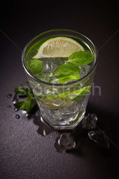 Refreshing cold Caipirinha with fresh lime slices and ice on a dark slate Stock photo © artjazz