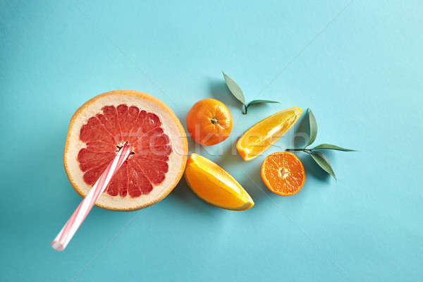 Different citrus with straws and leaves on a blue paper background top view. Healthy drink Stock photo © artjazz