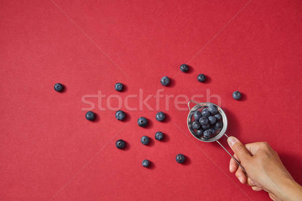 A womens hand holds a colander with red ripe sweet blueberry on a red paper background. Stock photo © artjazz
