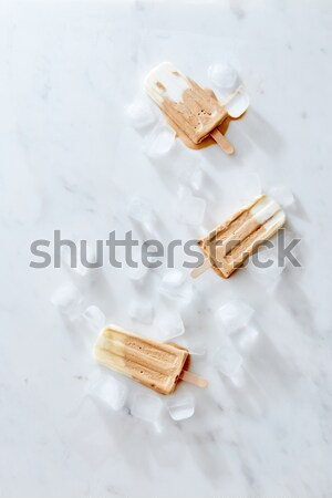 Frozen coffee gelato ice cream with coffee beans on a wooden stick over marble background, top view Stock photo © artjazz