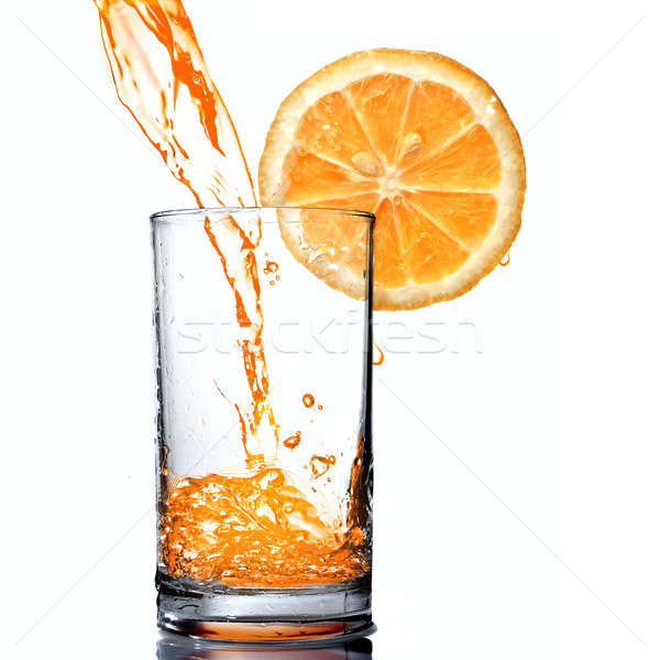 orange juice pouring into goblet with orange slice Stock photo © artjazz