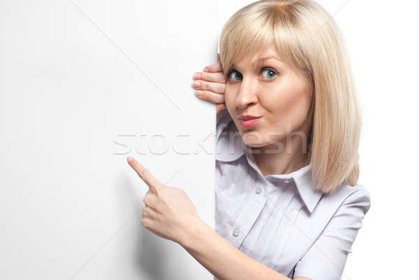 Stock photo: Attractive smiling woman holding white empty paper and pointing on it isolated on white
