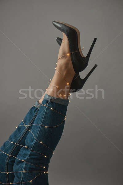 The legs of a woman are stretched out decorated with a Christmas garland Stock photo © artjazz